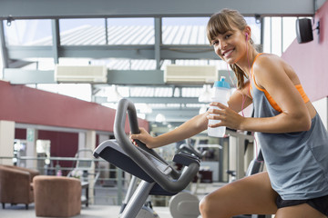 Happy young woman drinking water while exercising on a machine in gym