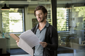 Close-up of a happy man reading a file
