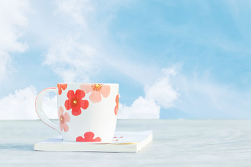 Closeup cute cup of coffee white book on blurred concrete desk in the garden with beautiful blue sky with cloud in the morning textured background