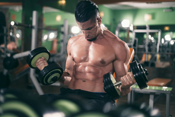 Muscular guy lifting weights in the gym