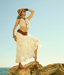 Fashion shot of a beautiful boho style woman standing on a rock near sea. Boho outfit, hippie, indie style