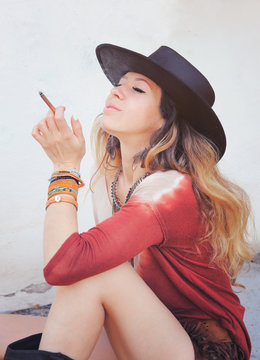 Beautiful woman enjoy smoking a cigarette, outdoor photo,  dressed in boho chic style outfit