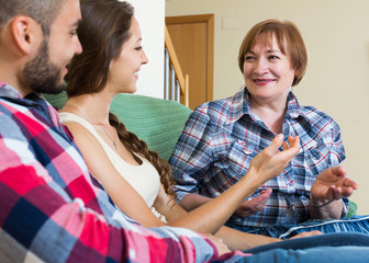 couple sitting in living room and talking with mother