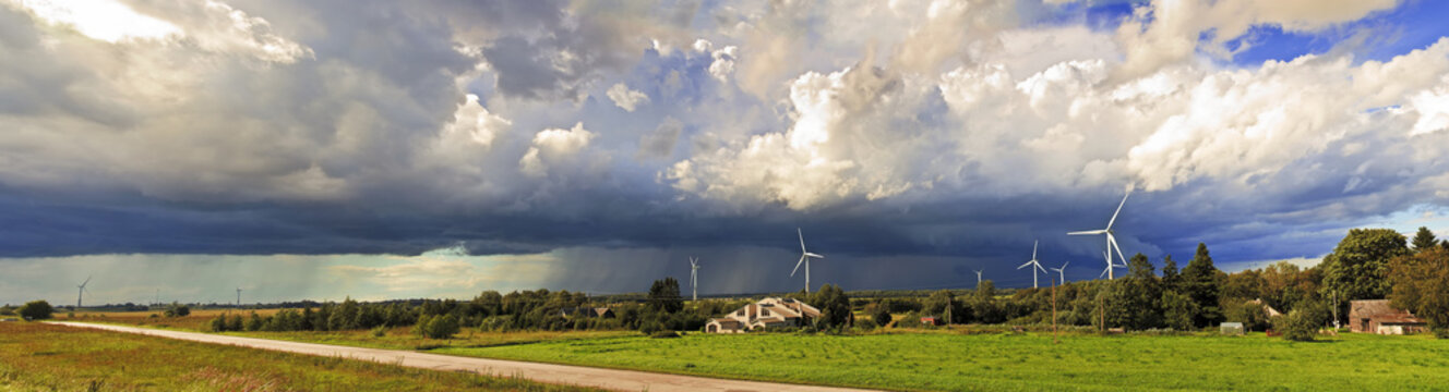 Panorama of windmills on rural field in the storm clouds and rain. Wind turbines panorama in countryside.