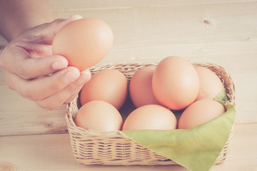 hand holding egg on wooden background with filter effect retro v