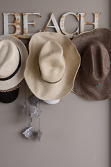 Hat rack with straw beach hats and a silver fish wind chime.