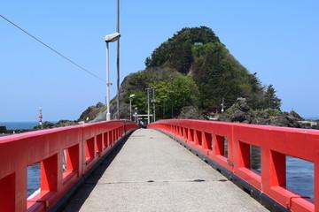 東北の江ノ島  白山島 / 山形県鶴岡市の由良海岸沖にある白山島は、「日本の渚百選」と、「快水浴場百選」に選ばれた由良海岸のシンボル的な島で、その景観から「東北の江ノ島」と呼ばれています。由良海岸から島までは赤い白山橋が架けられており、歩いて島に渡ることが出来ます。