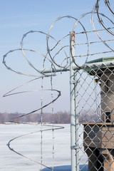 Razor Wire Around Building – Razor wire on top of barbed wire and chain link fence, protecting a building.