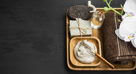 Skincare spa with clay mask,natural soap and oil in wooden tray