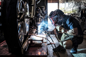 Mechanic in protective helmet working with welding