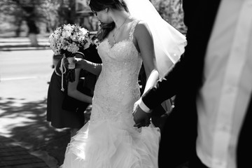 Wind blows bride's veil while a groom holds her hand tightly
