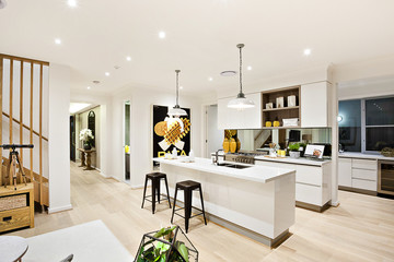 Modern kitchen with white walls illuminated by hanging lamps