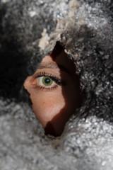 Weibliches Auge - Frau schaut durch Loch in der Wand
