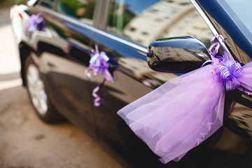 Black wedding car decorated with the purple fatin