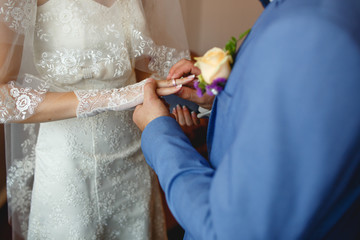Groom is putting on a ring to the bride's finger