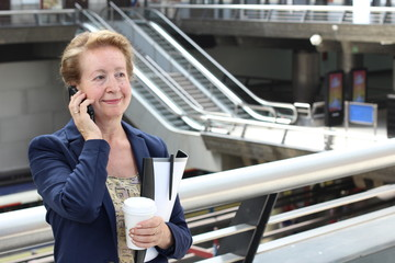 Business woman in the airport or train subway metro station making a phone call with smartphone