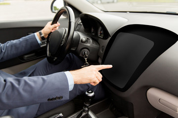 man driving car and pointing to on-board computer