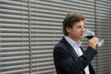 Portrait confidant vintner drinking red wine in winery