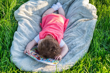 The little girl fell asleep on the book. She lies on the grass in the park.