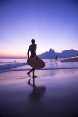 Sunset silhouette of carioca Brazilian running with skimboard on Ipanema Beach Rio de Janeiro, Brazil