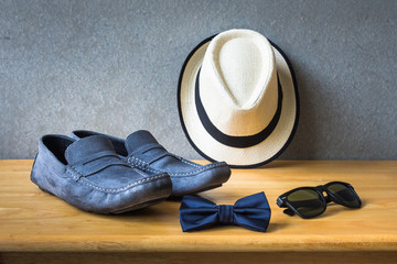 Men's casual outfits with blue shoes, bow tie, hat and sunglasses on wooden table over wall grunge background