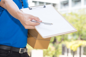Delivery Man holding parcel and giving pen to client