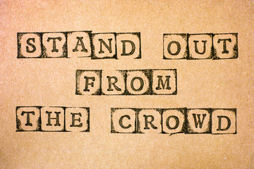 Words Stand Out From The Crowd make by black alphabet stamps on cardboard