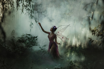 Fantastic photo shoot with smoke. Fairy Coquette walking in the fog. Background fairy forest, vines and trees. Unusual fabulous looks, purple dress and torn wings. Fancy toning. Wall mural