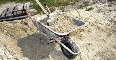 A pile of sand, a shovel and a construction truck for transporta