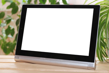 The tablet stands on wooden table on green background. Layout.
