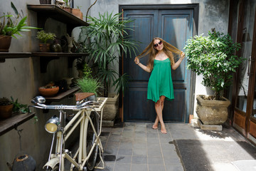 the young stylish hipstersky beauty, green dress, black sunglasses, tropical resort hotel, walking, sexual, the invitation, the island of travel, an exotic garden,the coquettish, sending kiss