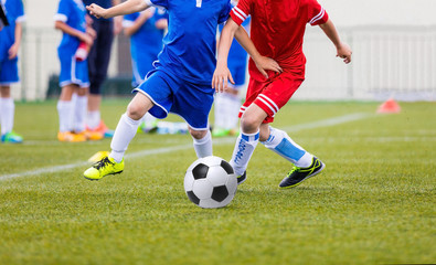 Young soccer players kicking football ball.