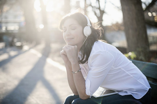Mature woman listening to music and sitting in the park bench, Bavaria, Germany