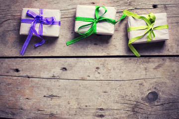 Three festive gift boxes with presents on vintage wooden backgro