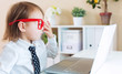 Toddler girl wearing big red glasses while using her laptop