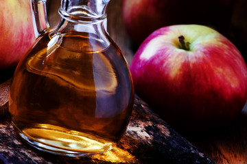 Homemade apple cider vinegar in a carafe, black background, sele