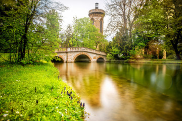 View on the bridge and tower of Franzensburg castle in Laxenburg town in Austria. Long exposure image effect with glossy water and reflection.