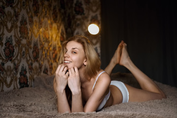 Naked pretty girl lying on bed with crossed legs. Happy smiling