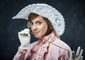 Woman in vintage dress and hat  with monocle.