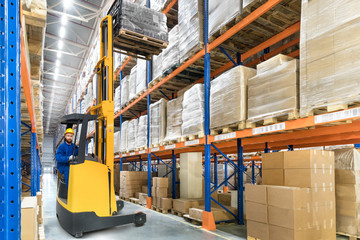 Young forklift driver in big distribution warehouse