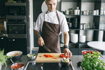 Young student in apron cutting vegetables