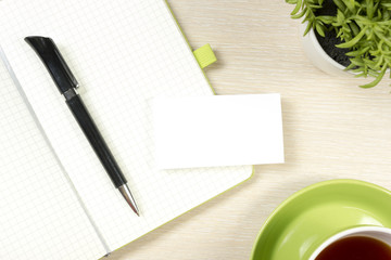 Business card blank, notepad, coffee cup and pen, flower at office desk table top view. Corporate stationery branding mock-up