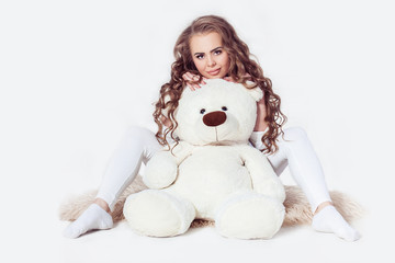 Sexy young blonde girl wearing in wight clothes sitting with teddy bear on white background. Image released. Isolated.