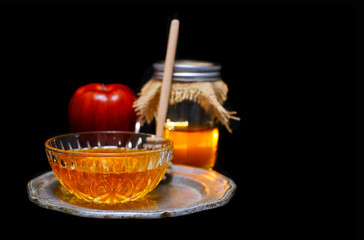 Rosh Hashanah low key image of honey and apple on a pewter plate. The honey is in a crystal bowl and in a canning jar with burlap top. All on a black background with copy space.
