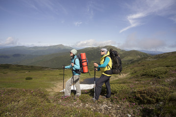 Summer hiking in the mountains with a backpack .