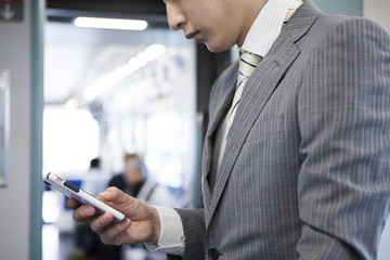 Businessman is looking at the smartphone much on a train