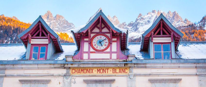 panorama background of facade of Chamonix train station near Mont Blanc, France, French Alps and mountain peaks lightened with sun