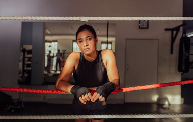 Portrait of female boxer leaning on ropes