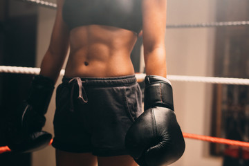 Abdomen of female boxer standing in ring