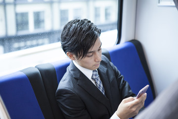 Businessman has become addicted to smart phone on a train